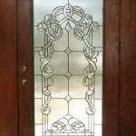 شیشه استیند گلس ساخته شده برای درب چوبی ورودی تک لنگه ،که در ساخت شیشه تیفانی آن از شیشه های الماس تراش شفاف برای فرم های کلاسیک در هم تنیده طرح و شیشه بافت دار بی رنگ برای قسمت زمینه طرح استفاده شده است.