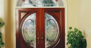 در این تصویر به دلیل فرم خاص درب ورودی که به صورت شیشه خور نیم دایره به صورت دو لنگه که کنار هم یک دایره کامل را تشکیل میدهد و همچنین کتیبه بالای درب شکوه خاصی به ورودی این منزل داده است.در این پروژه هنرمند برای ساخت شیشه های استیند گلس یا تیفانی از موتیف کلاسیک در طراحی استفاده کرده که در ساخت شیشه ها نیز فقط از شیشه های بافت دار و شیشه قرمز رنگی که خیلی ظریف و هوشمندانه در کار خودنمایی میکند استفاده کرده است.